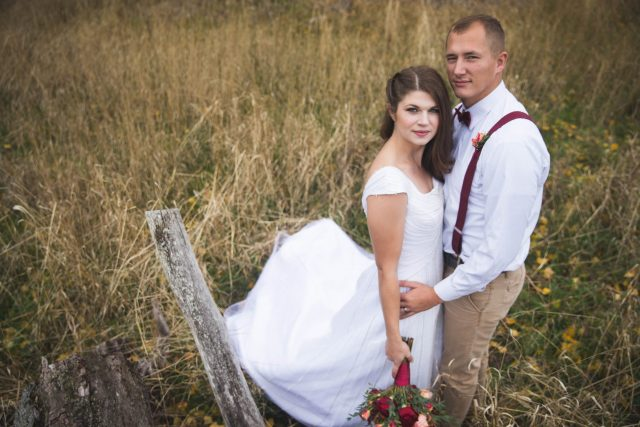 Photo looking down at bride and groom in field of grass