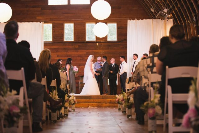 Bride and Groom exchange rings during ceremony in big barn