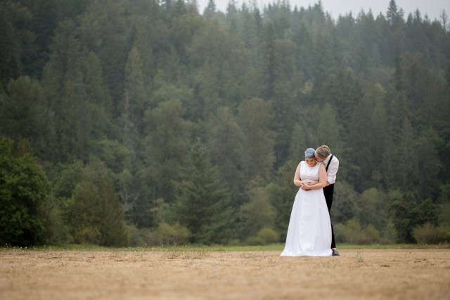 Tacoma bride and groom stand in field in front of evergreen hill