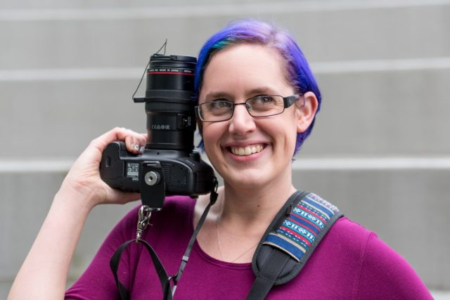 Girl with purple hair holds camera close to face