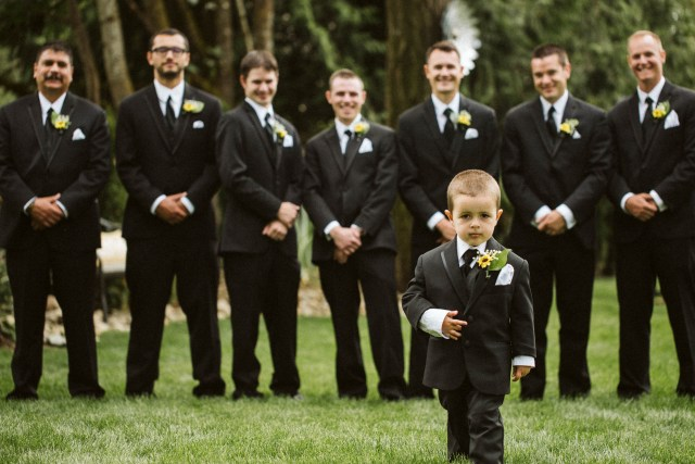 Young ring bearer stands in front of groom with groomsmen.