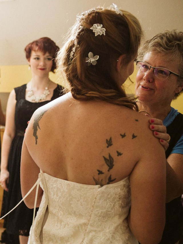 Mother of bride talks to bride while getting ready for the wedding