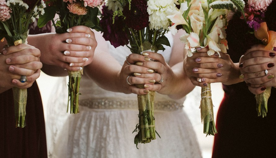 Bride and bridesmaids hold bouquets together
