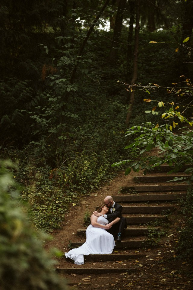 Bride and groom sit next to each other and lean in together on outdoor stairs.