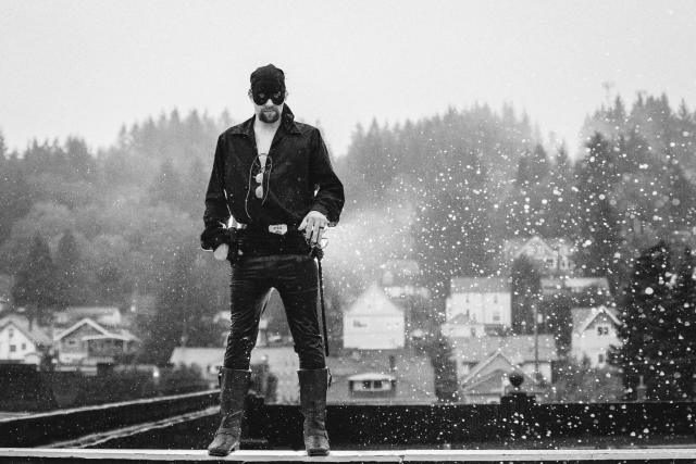 Groom dressed as The Dread Pirate Roberts stands in front of view with rain lit up around.