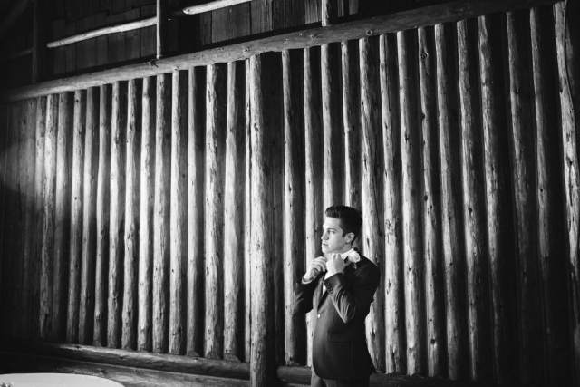 Washington Groom stands in front of wood log wall adjusting his bowtie