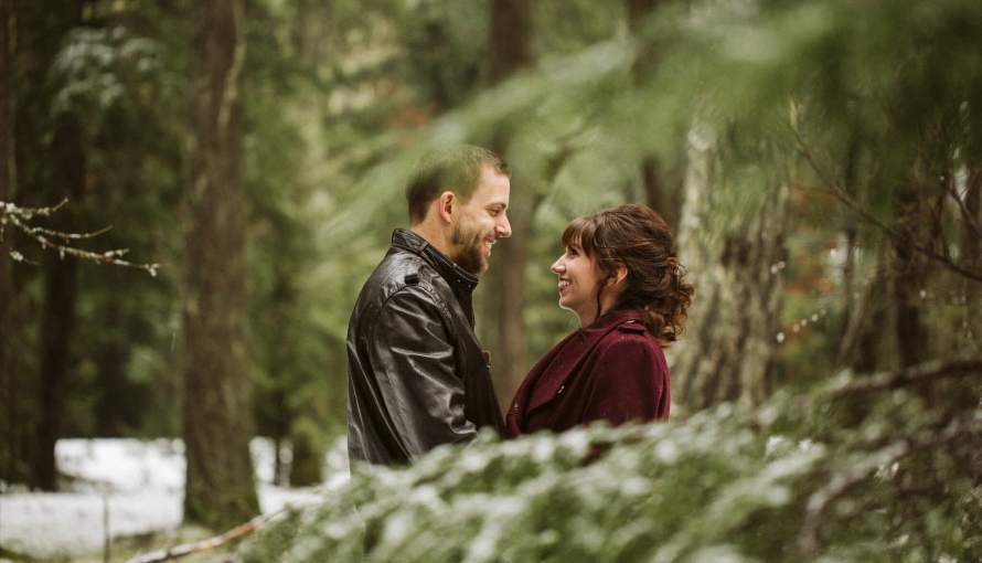 Husband and wife smile at each other beside an evergreen tree with light snow in Washington