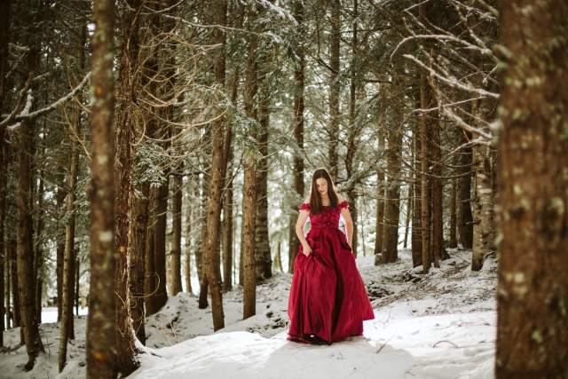 Teen girl walks down snowy bump in forest with snow