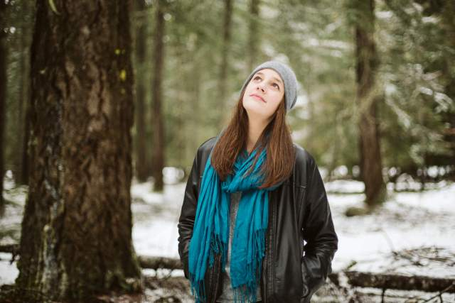 Teen girl looking up at the trees with leather jacket and blue scarf