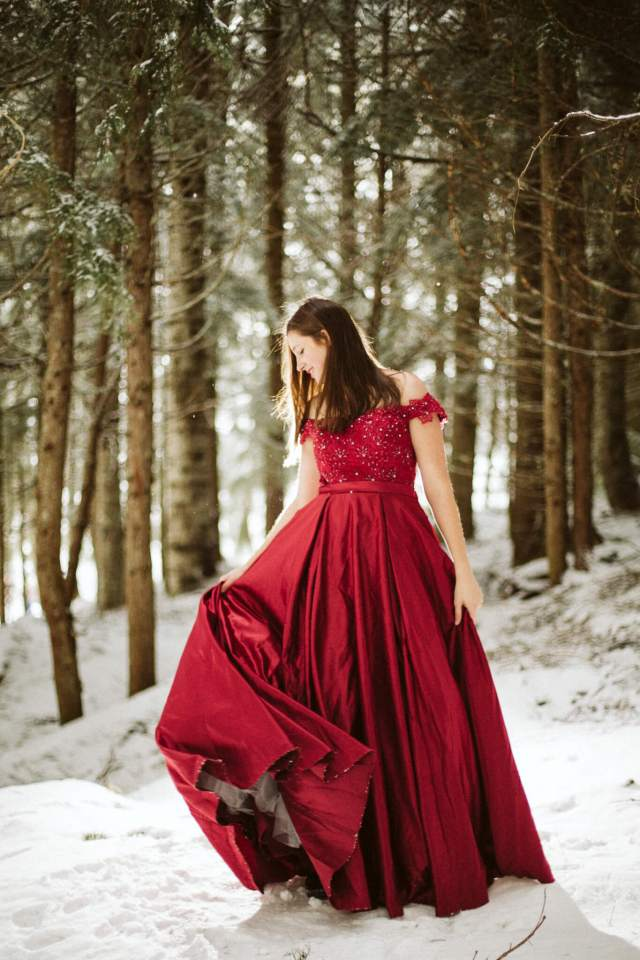 Teen girl in red prom dress stands in snow while swishing skirt