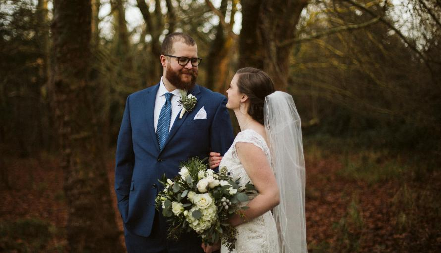 Groom stands with bride holding his arm looking at him in front of a bare winter tree