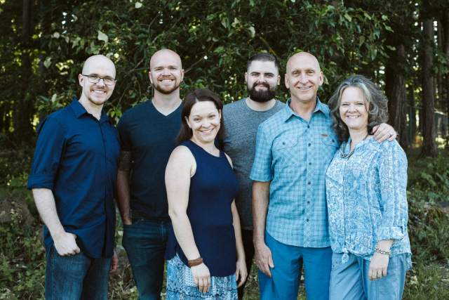 Family with four adult children stand together with blue shirts in front of forest