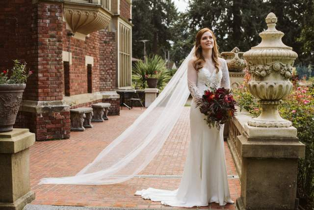 Picture of the bride standing with an outstretched veil outside of Thornewood Castle.