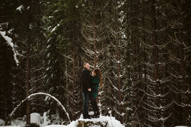 Man and fiance stand on snowy stump in front of tall, dark pine forest