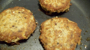 No-filler salmon patties cooking in a frying pan.