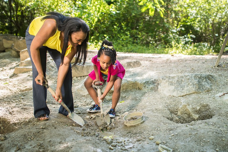 A mother and daughter dig in the fossil site with shovels.