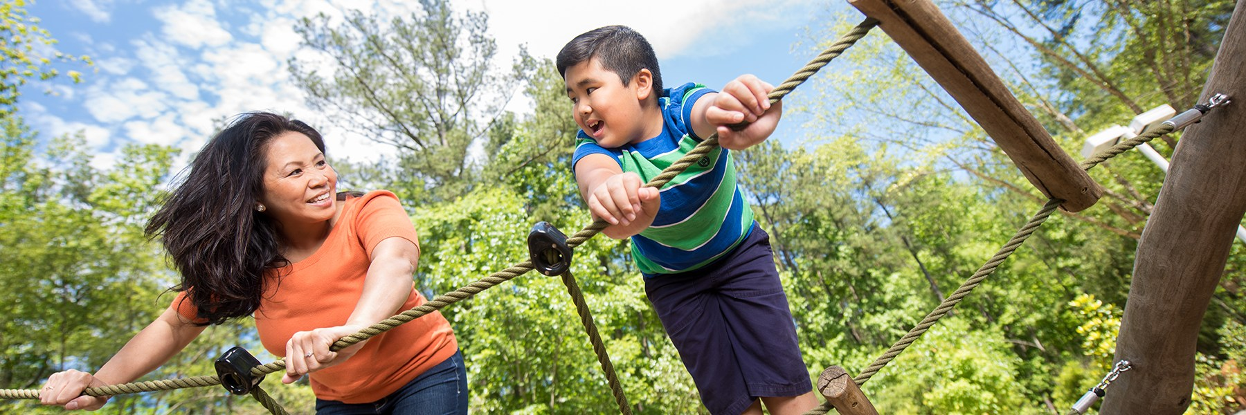 A woman and boy look at each other atop a rope bridge climber.