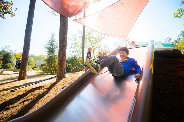 A boy in a superman shirt goes down a wide hillside slide.