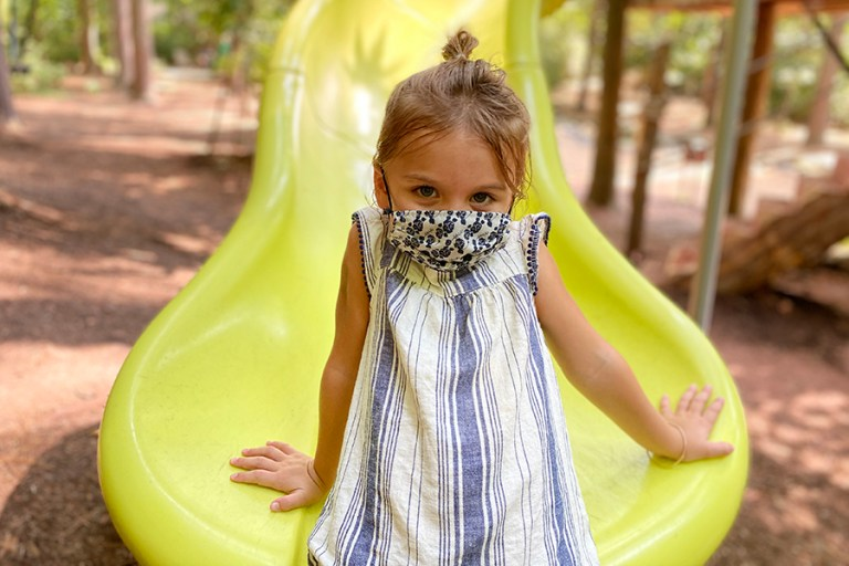 A young girl sits on a slide, wearing a mask.