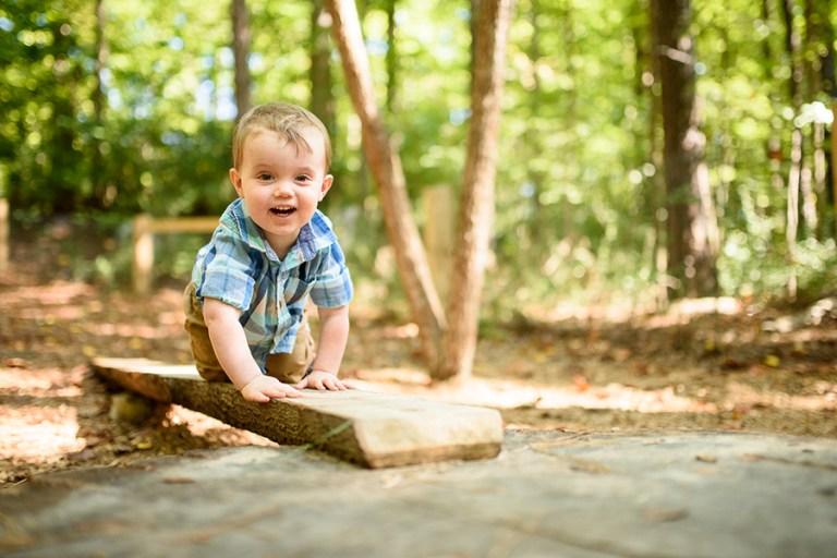 A small boy climbs on a board toward the camera.