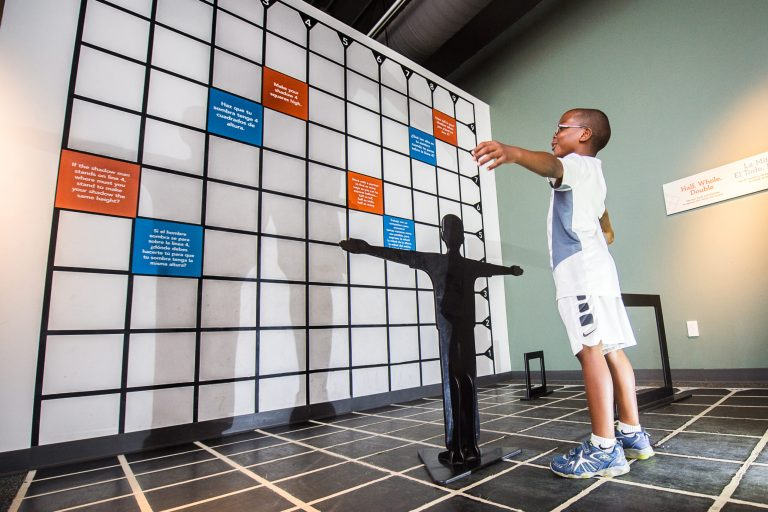 A boy stretches his arms wide in front of a giant grid wall, casting a shadow.