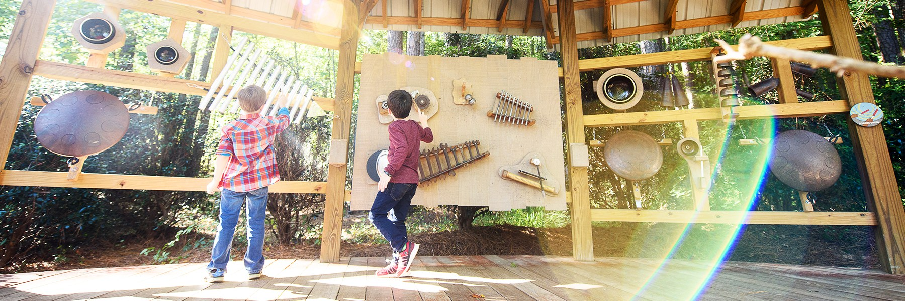Two boys play a wall of instruments outside.