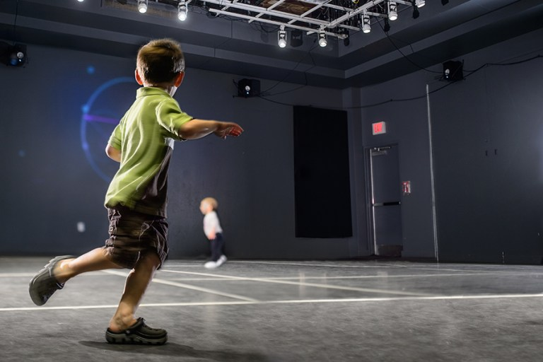 A boy runs through a room that plays sounds.