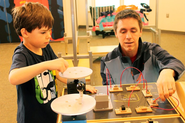 A boy and man work at a circuit table.