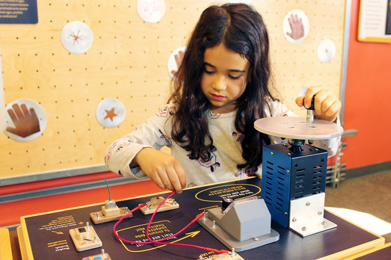 A young girl is playing with a circuit table.