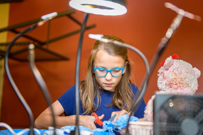 A girl works under a series of lights on a project.
