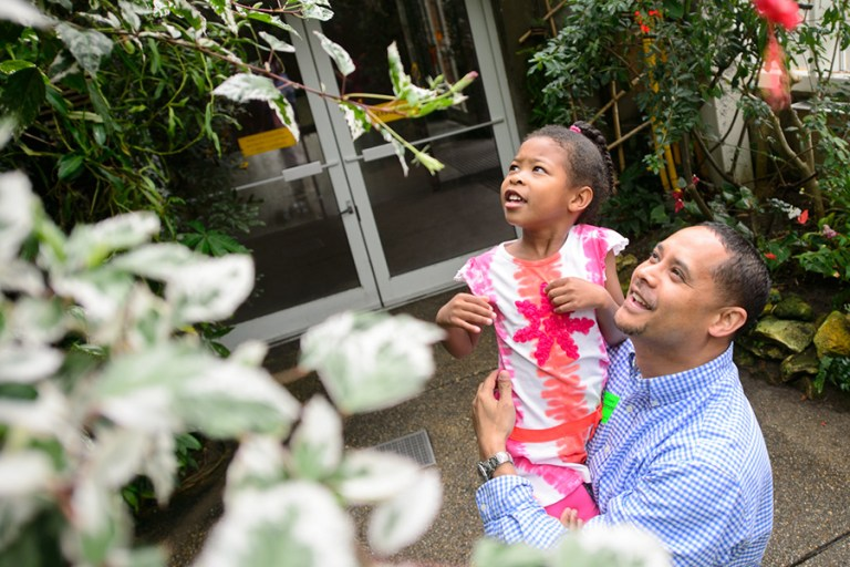 Man holds a little girl up in the air to look at the tropical plants.