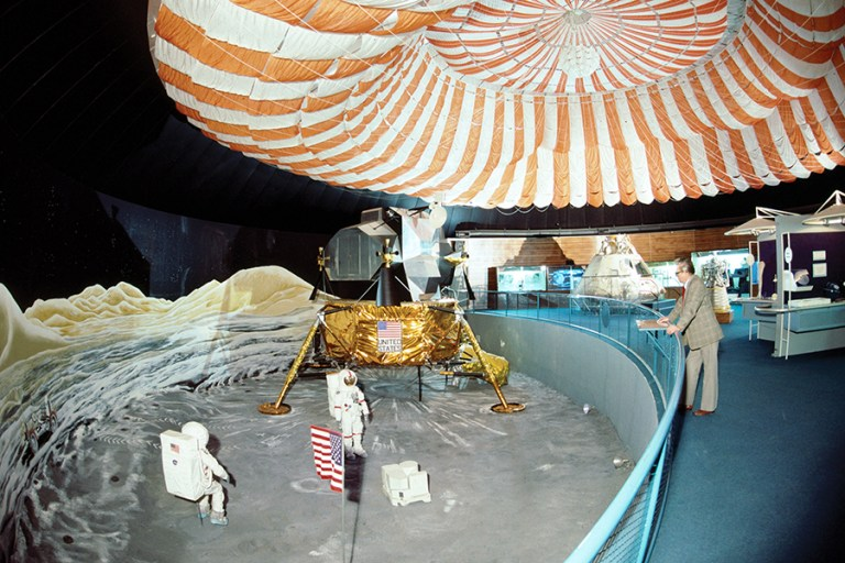 An overhead view of the Aerospace gallery in the 1970s featuring a lunar scene and a giant red and white parachute.