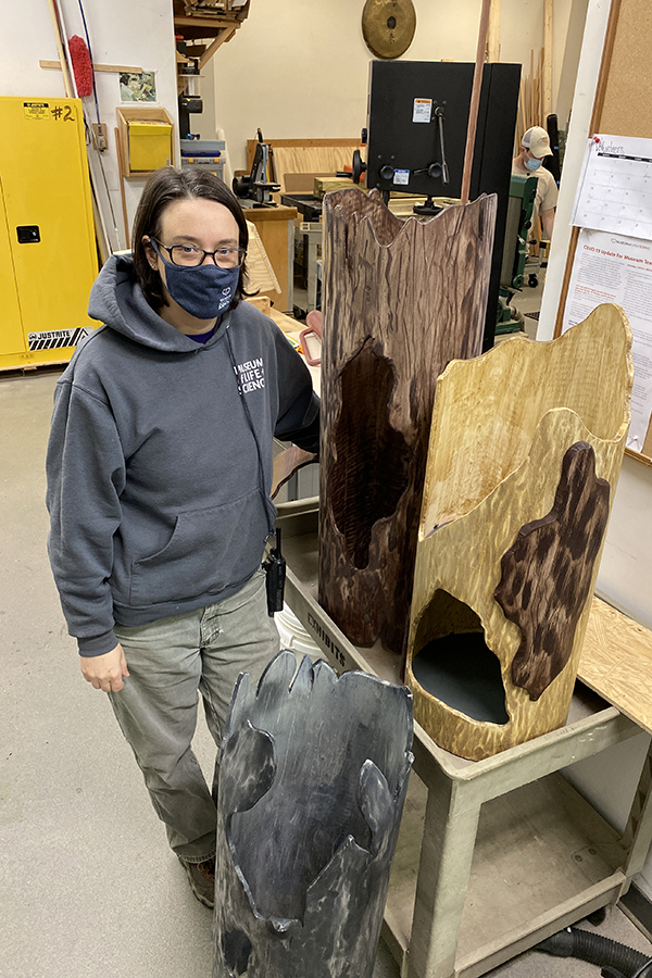 Staff member stands next to logs