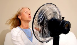 Lady with fan hot flushes