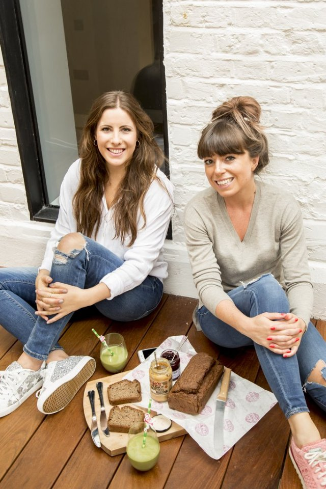 Two woman sitting against a wall and eating healthy vegan snack