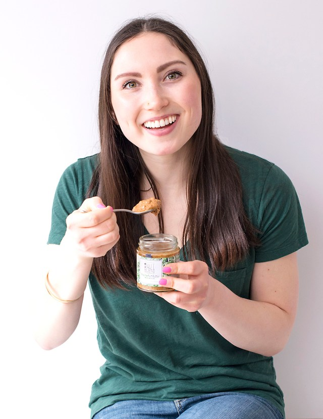 A woman scooping Nut Blend from a jar with a spoon