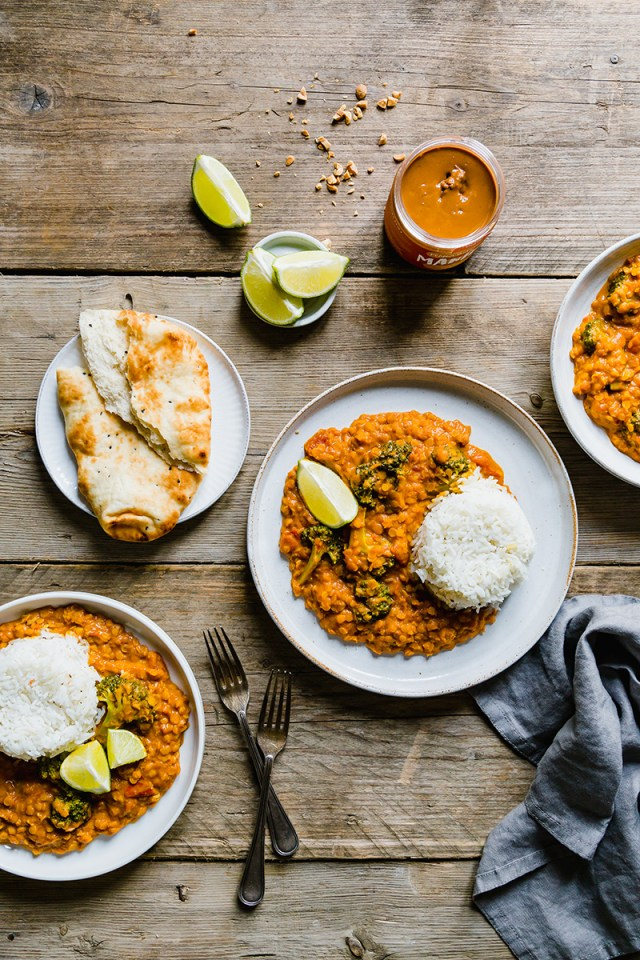 Three plates of peanut lentil curry with naan bread