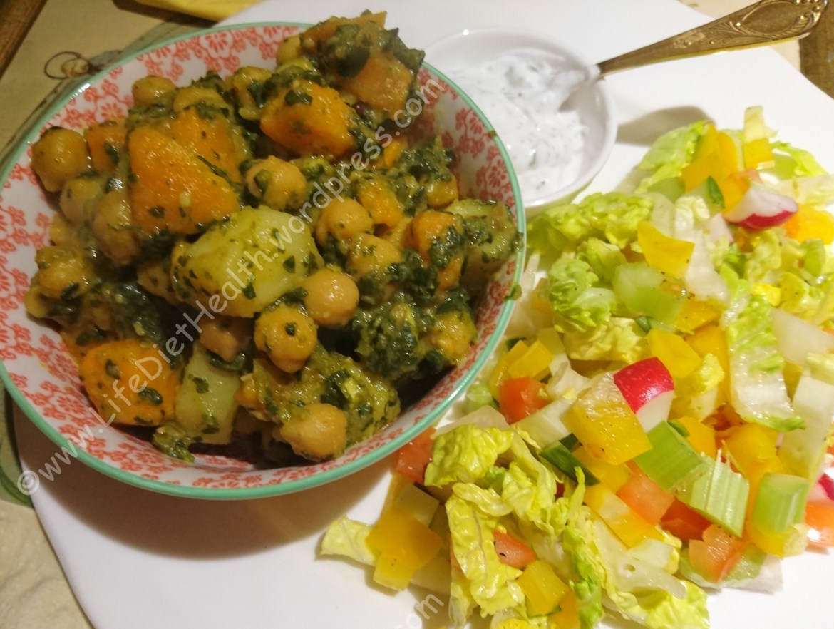 Dish or chickpea, potato and spinach curry with salad and raita sides