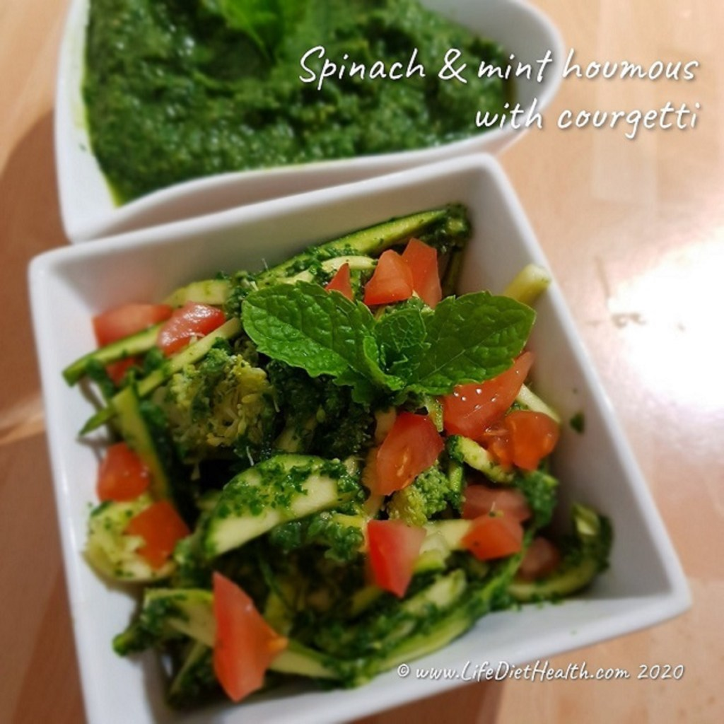 Square white bowl with courgetti dressed in green spinach houmous, topped with pieces of fresh tomato and a sprig of mint.