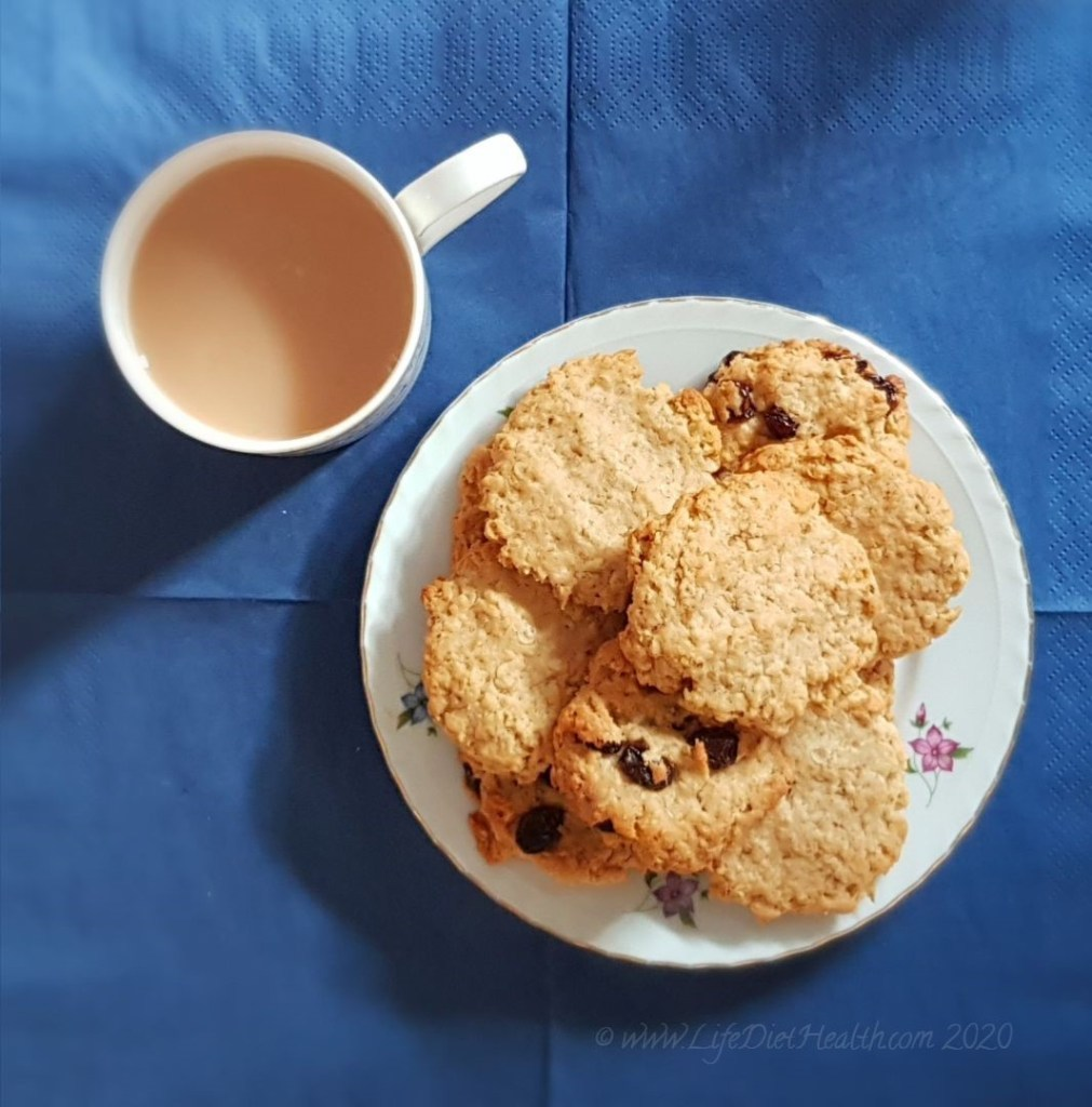 Birds eye view of a plate of plain and raisin cookies with a cup of tea, on a navy blue background.
