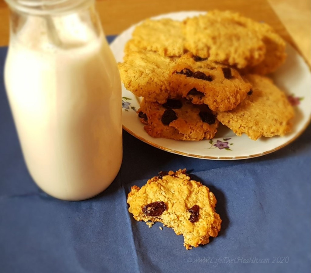 A cookie with a bite out of it in-front of a plate of cookies and a bottle of milk.