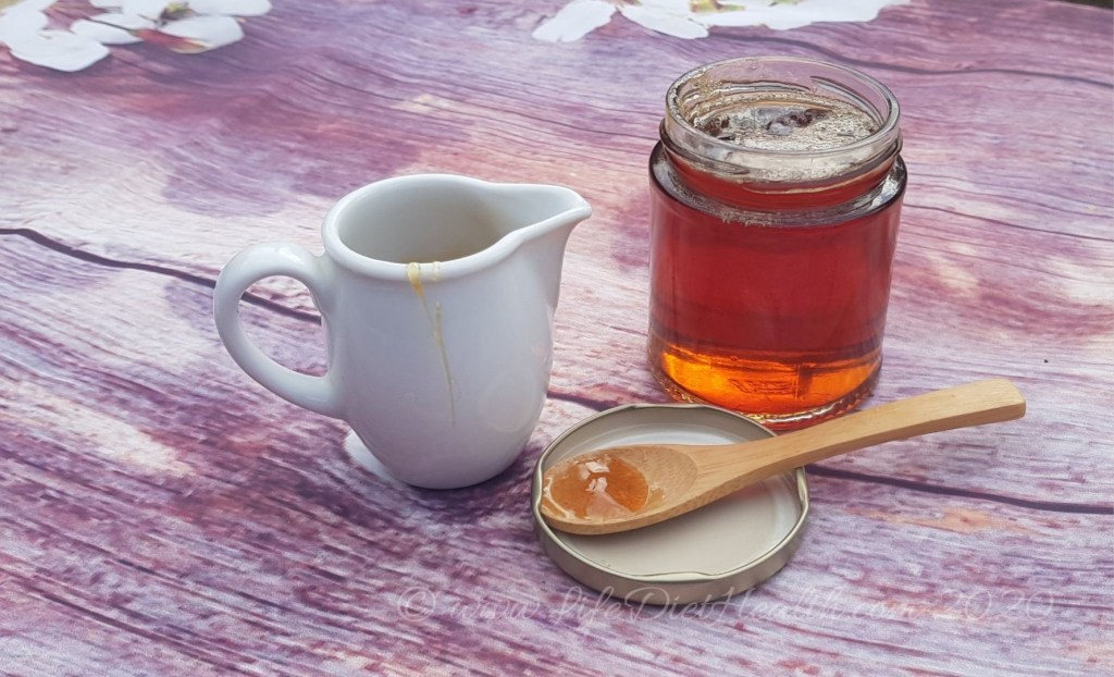 Glass jar of golden coloured Dandelion honey - syrup, with a white jug and teaspoon sized wooden spoon.