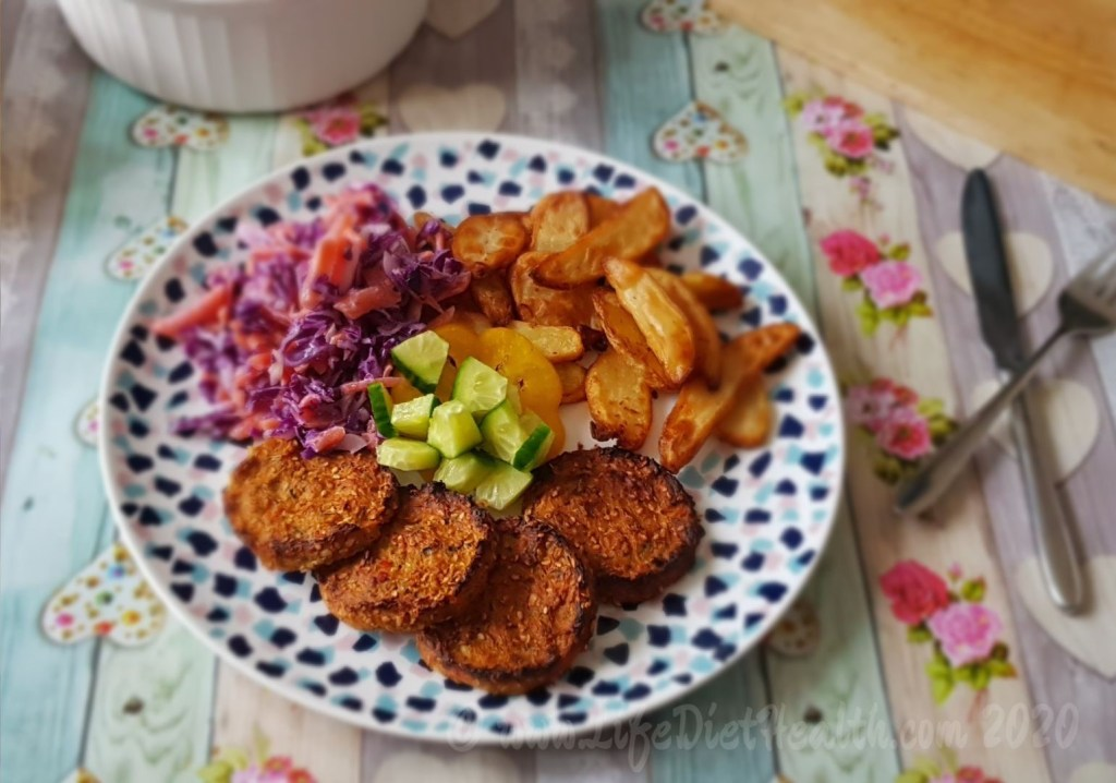 4 vegetable burgers on a mosaic plate with potato wedges, coleslaw and salad.