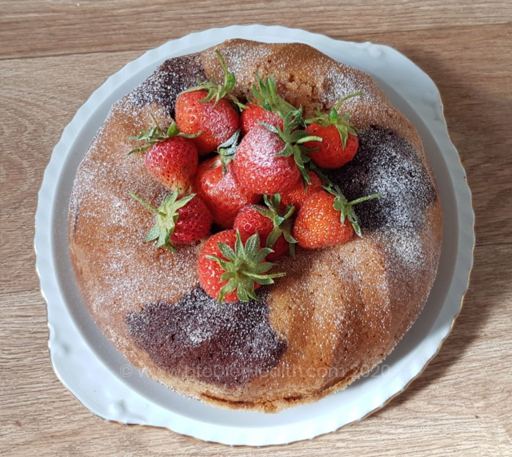 Marbled Vegan Bundt Cake filled with fresh strawberries and dusted with icing sugar.