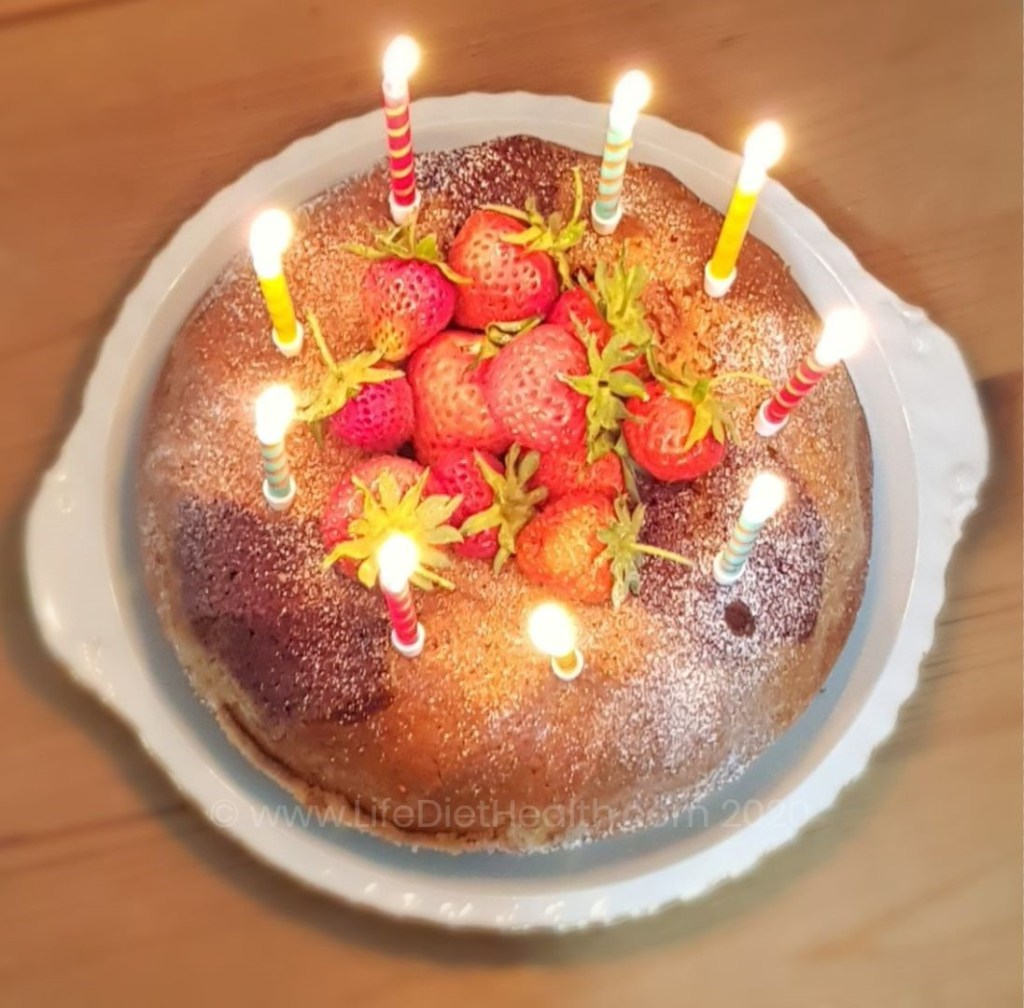 Bundt cake on a white plate, filled with fresh strawberries and decorated with 9 candles