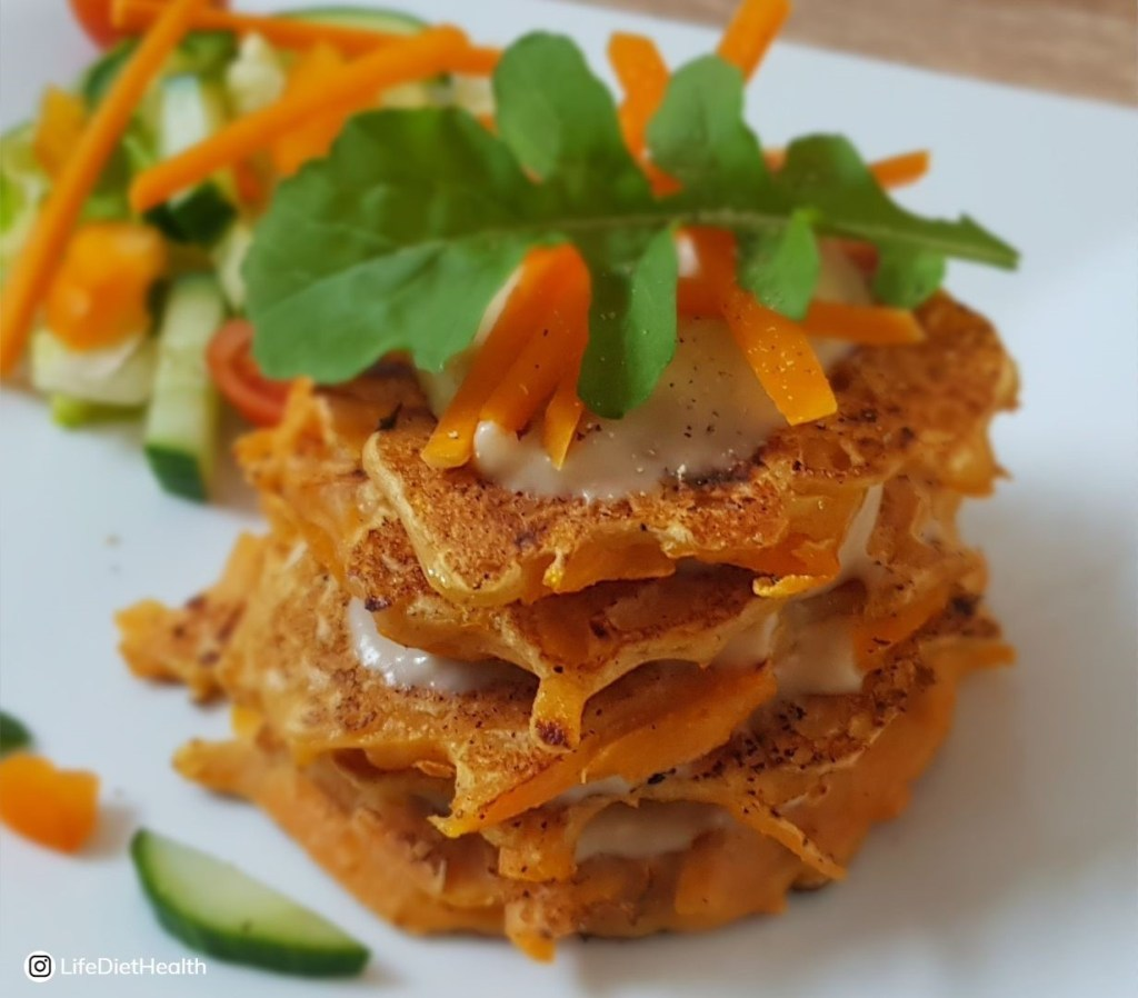 Stack of savoury pumpkin pancakes on a plate, topped with rocket.