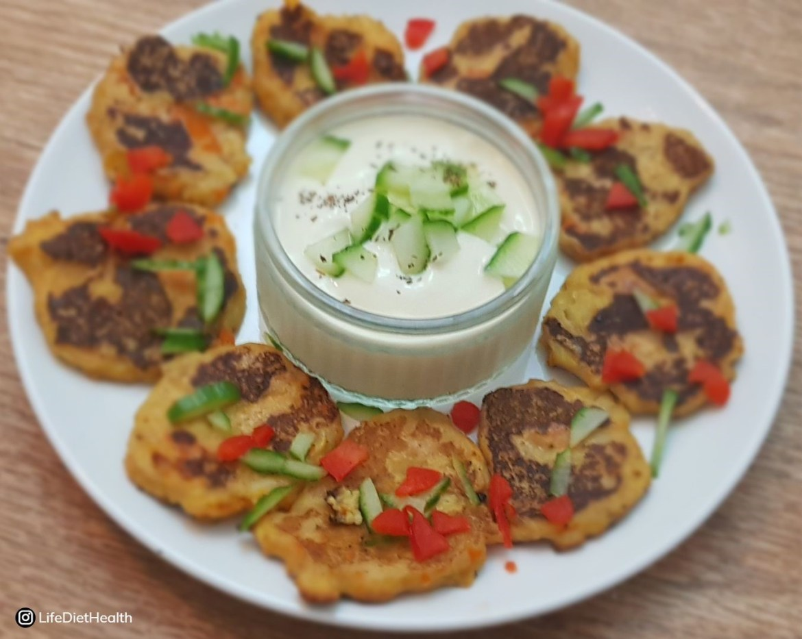 Plate of vegetable mash fritters on a white plate, with raita dip in centre