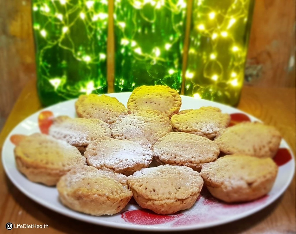 Plate of mince pies with green bottle lights for Seasons Greetings.