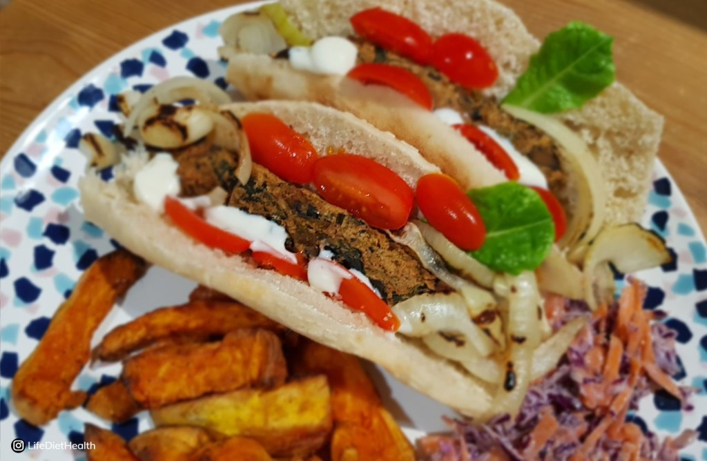 veggie sausages in a roll, on a plate with coleslaw and sweet potato fries