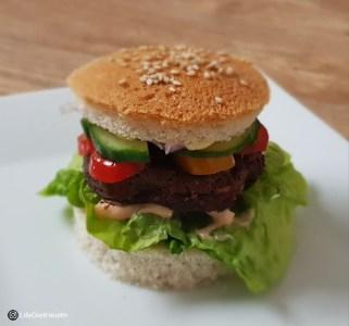 burger in a bun on a white plate